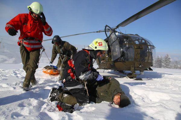 Foto rechts: Der verletzte Insasse des abgestürzten Hubschraubers wird medizinisch versorgt und dann abtransportiert.
