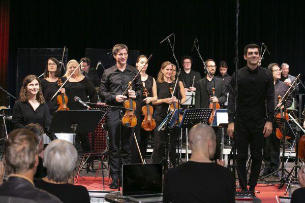 """Texterin Katharina Klein (links), Konzertmeister Pawel Zalejski (Mitte), das SOV und Dirigent Ektoras Tartanis (rechts) beim Applaus für """"Wartezeitenmusik"""" von Gerda Poppa.maurice Shourot"""