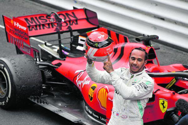 Hamilton deutet im Ziel auf seinen Helm mit Lauda-Schriftzug und Lauda-Design. AFP