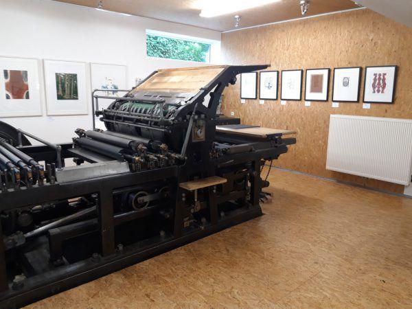 Bild rechts: 2010 zeigte Markus Gell der NEUE seine damals neu erworbene Druckmaschine, die auch im großen Bild zu sehen ist. Oben: Werke von Hugo Ender (r.) und Herbert Albrecht.Lisa Kammann (3)/Bernd Hofmeister (1)