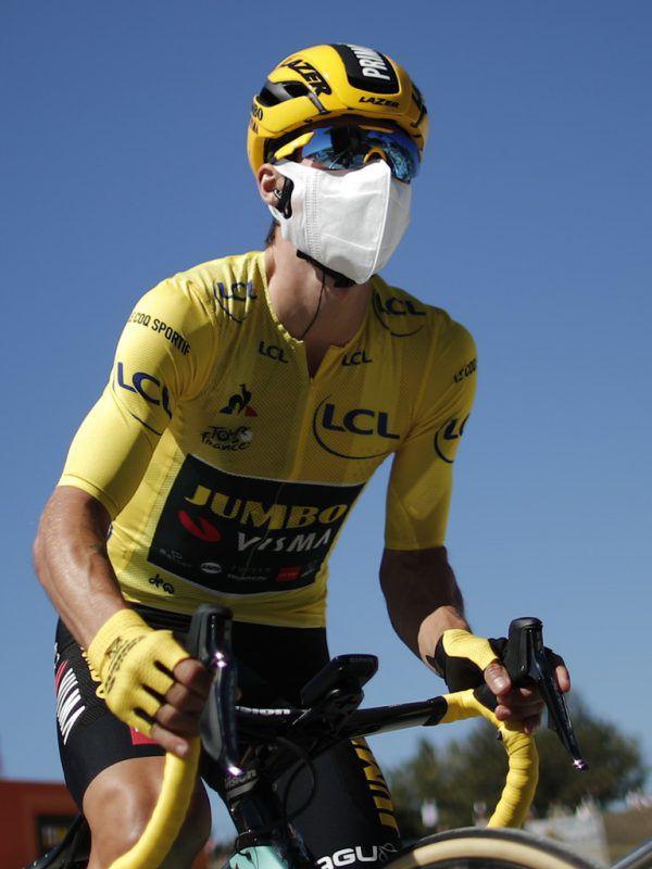 Primoz Roglic trägt eine Maske und das Gelbe Trikot.AP