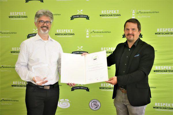 Jürgen Kessler (ÖGK) überreicht die Auszeichnung an DJW-Geschäftsführer Elmar Luger (l.). BGF