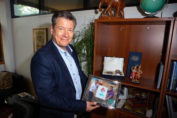 Jürgen Piffer vor dem Bild des aktuellen Königs von Thailand.Hartinger