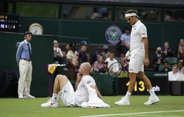 Roger Federer (r.) erkundigt sich nach dem Befinden von Adrian Mannarino.reuters